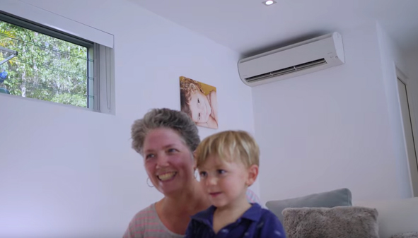 mother and son smiling with aircon in their back